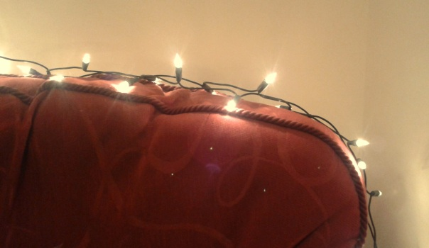 fairy lights on the back of a soft red armchair